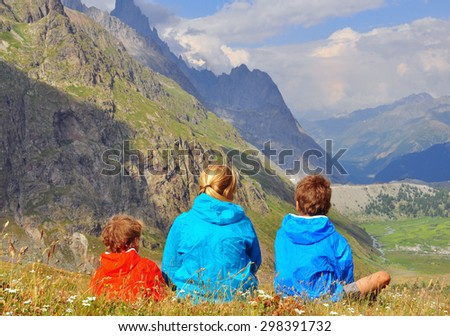Young woman with kids in mountains, back view - stock photo