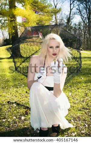 young woman with lace umbrella and glass ball in nature - stock photo