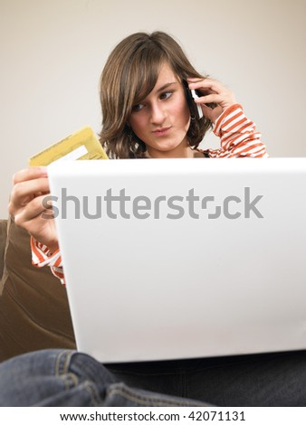 Young woman with laptop, holding credit card and talking on the phone. Vertically framed shot.