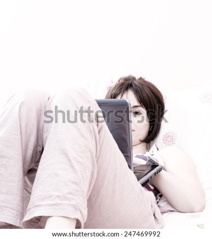Young woman with laptop in bed. - stock photo