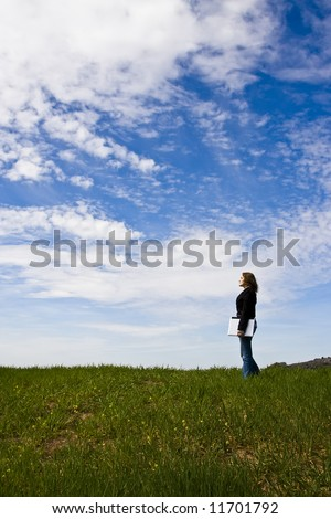 Young woman with laptop in meadow, copy space.