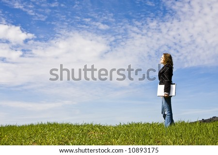 Young woman with laptop in meadow, coy space. - stock photo