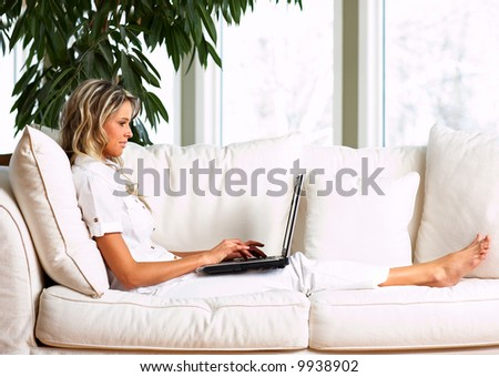 Young woman with laptop in the comfortable apartment - stock photo