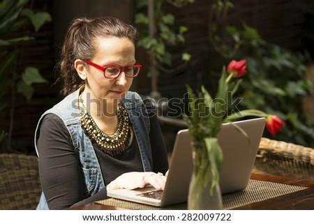 Young woman with laptop in the outdoor summer cafe. - stock photo