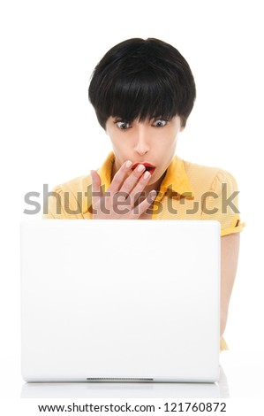 Young woman with laptop looking shocked - stock photo