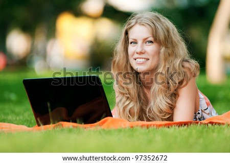Young woman with laptop on green grass at park - stock photo