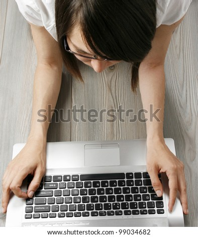 Young woman with laptop on the floor - stock photo