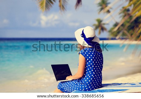 young woman with laptop on tropical beach vacation - stock photo