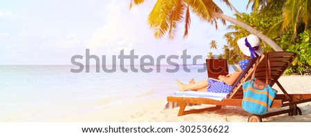 young woman with laptop on tropical vacation, panorama - stock photo