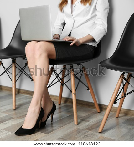 Young woman with laptop sitting on chair indoors - stock photo
