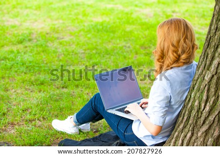 Young woman with laptop sitting on green grass in the park and relaxing - stock photo