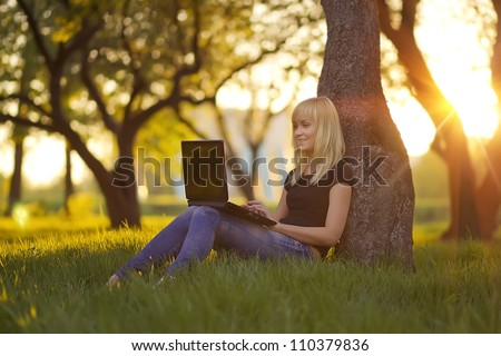 Young woman with laptop sitting on green grass in the park at sunset - stock photo