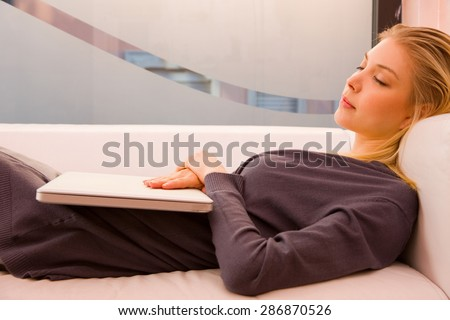 Young woman with laptop sleeping couch