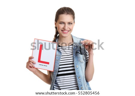 Young woman with learner driver sign and car key on white background