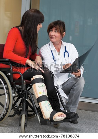Young woman with leg in plaster. Talking to a doctor - stock photo