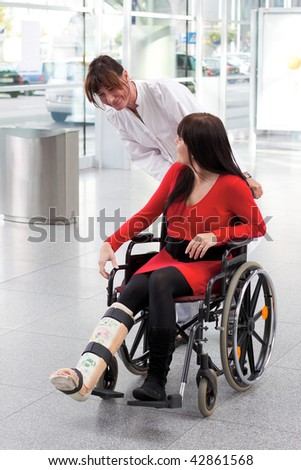 Young woman with leg in plaster, wheelchair and nurse - stock photo