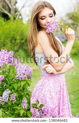 young woman with lilac flowers - stock photo