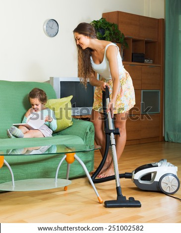Young woman with little daughter cleaning living room with vacuum cleaner  - stock photo