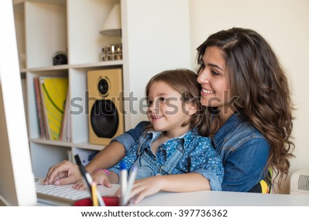 Young woman with little girl using computer at home - stock photo