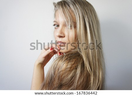 Young woman with long beautiful healthy blond hair, big green eyes and manicure