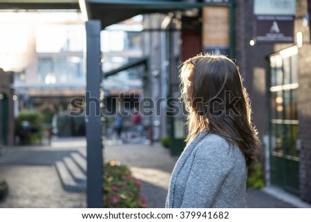 Young woman with long blond hair looking away on city street - stock photo