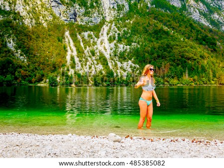 Young woman with long blonde hair stands in clear green lake water, enjoying nature in summer, lake Bohinj, Slovenia