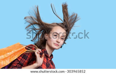 Young woman with long blowing hair and shoping bags isolated on blue background with copy-space