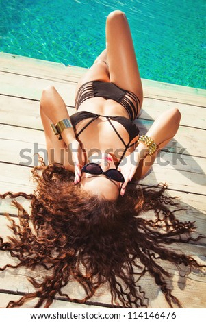 young woman with long curly hair in black bikini and sunglasses lay by the pool - stock photo