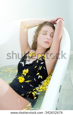 Young woman with long curly hair taking a bath with herbs and flowers. Spa and salon. Relax. - stock photo