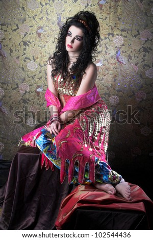 Young woman with long dark hair and in east costume - stock photo