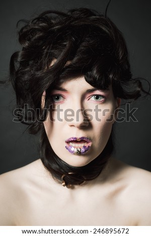 Young woman with long hair against a dark background with paillettes on the lips and a fibula in her hair - stock photo