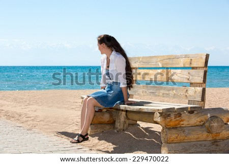 Young woman with long hair posing on a pier at the sea. - stock photo