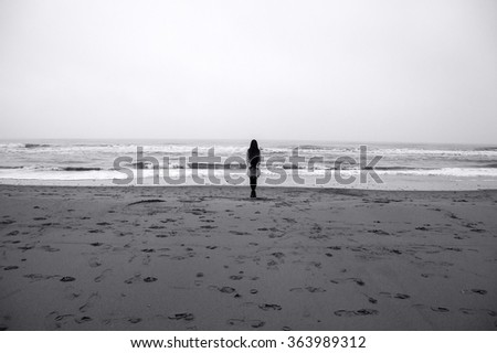 Young woman with long hair standing back on beach of the North Sea in cloudy evening. - stock photo