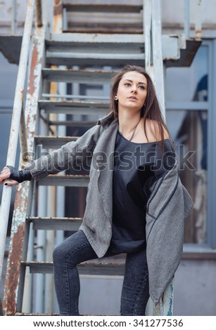 young woman with long hair, with a leather backpack, a warm hat, beautiful makeup, leather pants, a gray sweatshirt and a leather shirt, high heels walking one in the production hall and the street