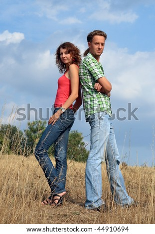Young woman with long wave hairs and attractive man are standing in the field and looking at us - stock photo