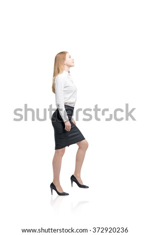 young woman with loose red hair in a blouse and skirt, high heels in the posture of making a step up. White background. Side view. Concept of office dress code. Isolated - stock photo