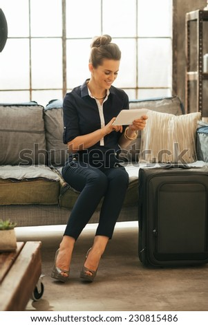 Young woman with luggage using tablet pc