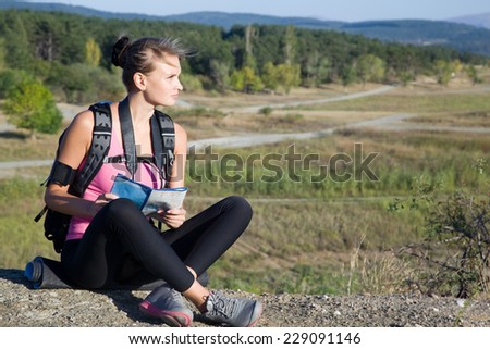Young woman with map in hand on a camping trip on vacation - stock photo