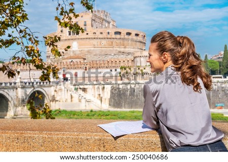 Young woman with map on embankment near castel sant'angelo in rome italy. rear view - stock photo