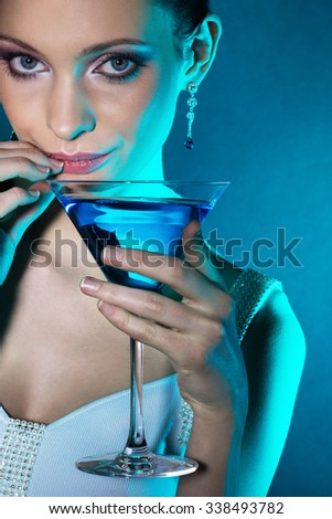 Young woman with martini glass in blue light. Focus on eyes. - stock photo