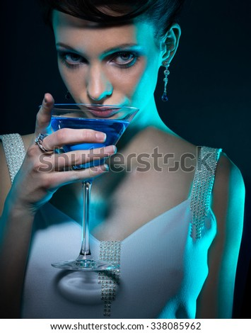 Young woman with martini glass in blue light on dark background. Focus on eyes. - stock photo
