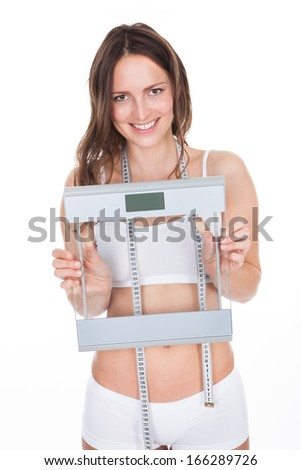 Young Woman With Measurement Tape Around Her Neck Holding Weight Scale - stock photo