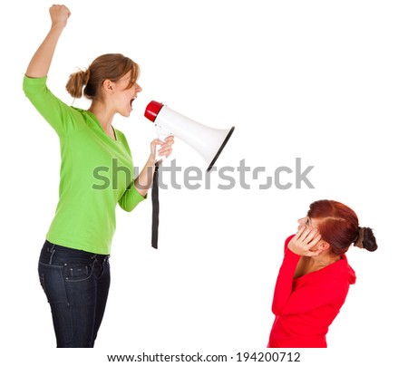 young woman with megaphone yelling at another one, white bckground - stock photo
