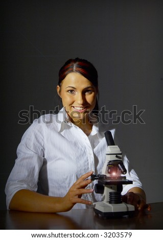 young woman with microscope - stock photo