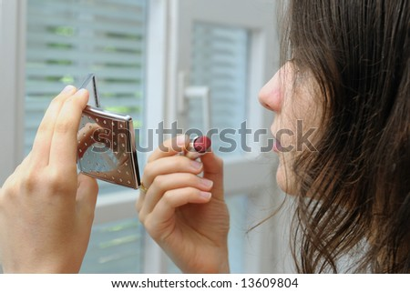 Young woman with mirror and lipstick - stock photo