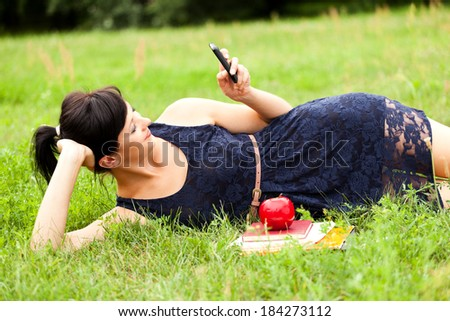 Young woman with mobile in the park, smiling - stock photo
