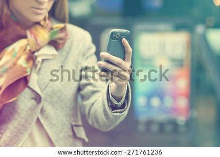 Young Woman with mobile phone, background is blured city - stock photo