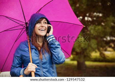 Young woman with mobile phone on rainy day - stock photo