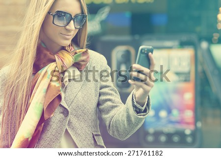Young Woman with mobile phone walking background is blured city - stock photo