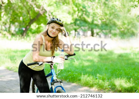 Young woman with mountain bike and bottle of water in hand